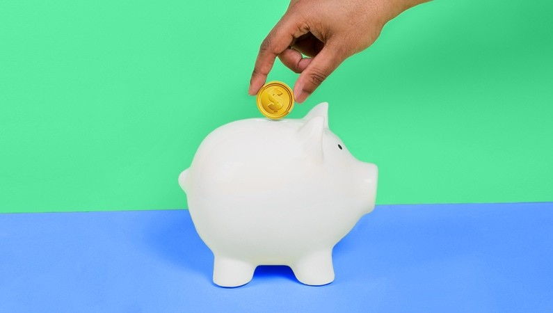 Cash flow problems | Person putting coin into a piggy bank