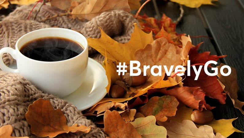 photograph of a cup of coffee and leaves with the text #BravelyGo