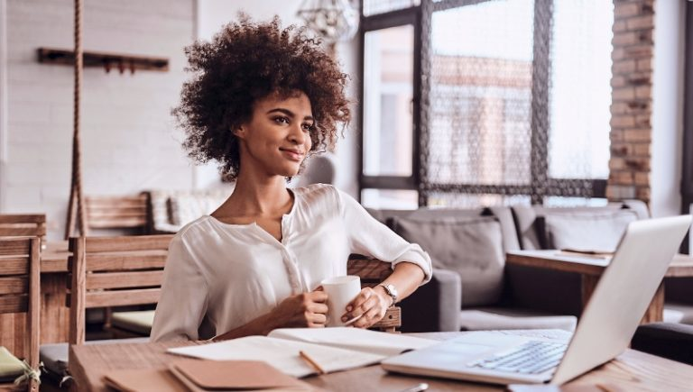 picture of a woman at a desk drinking coffee