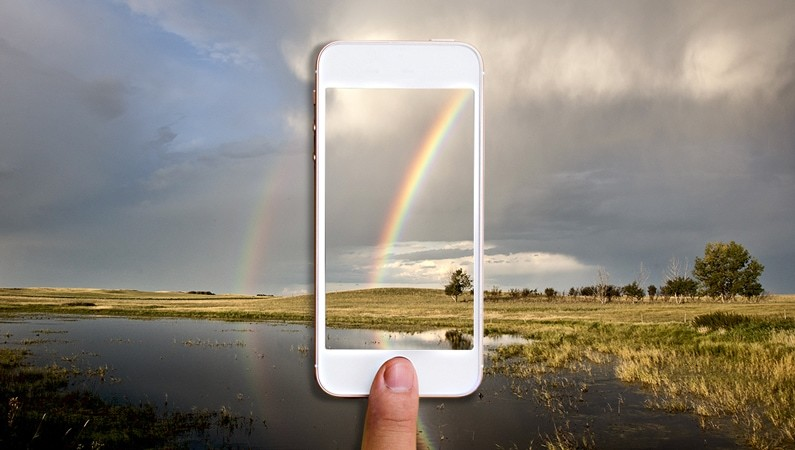 picture of someone taking a photo of a rainbow