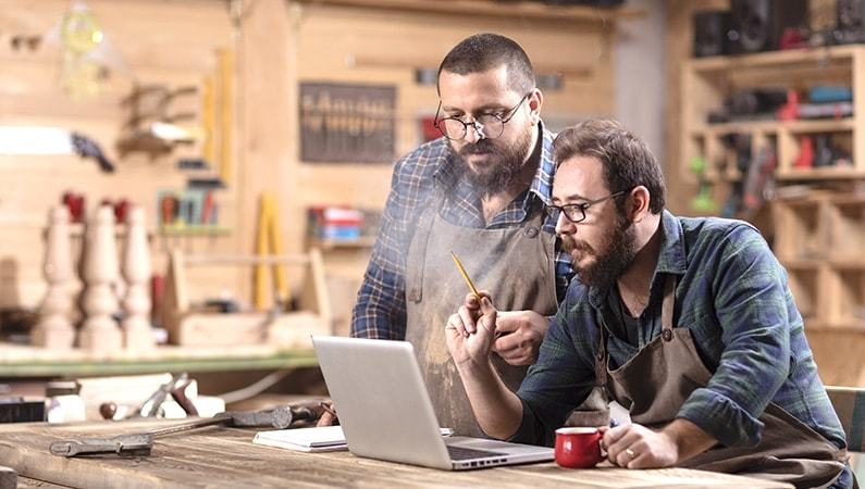 two woodworkers looking at a computer